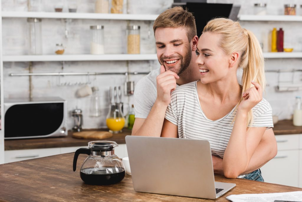 Happy boyfriend hugging girlfriend in kitchen while she using laptop