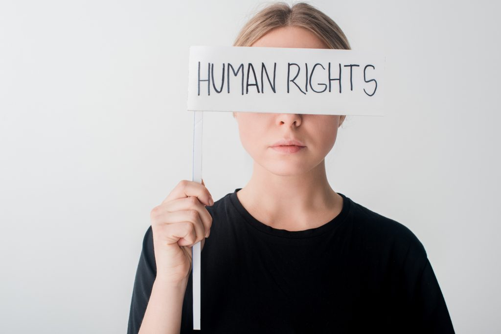 woman with human rights sign covering face