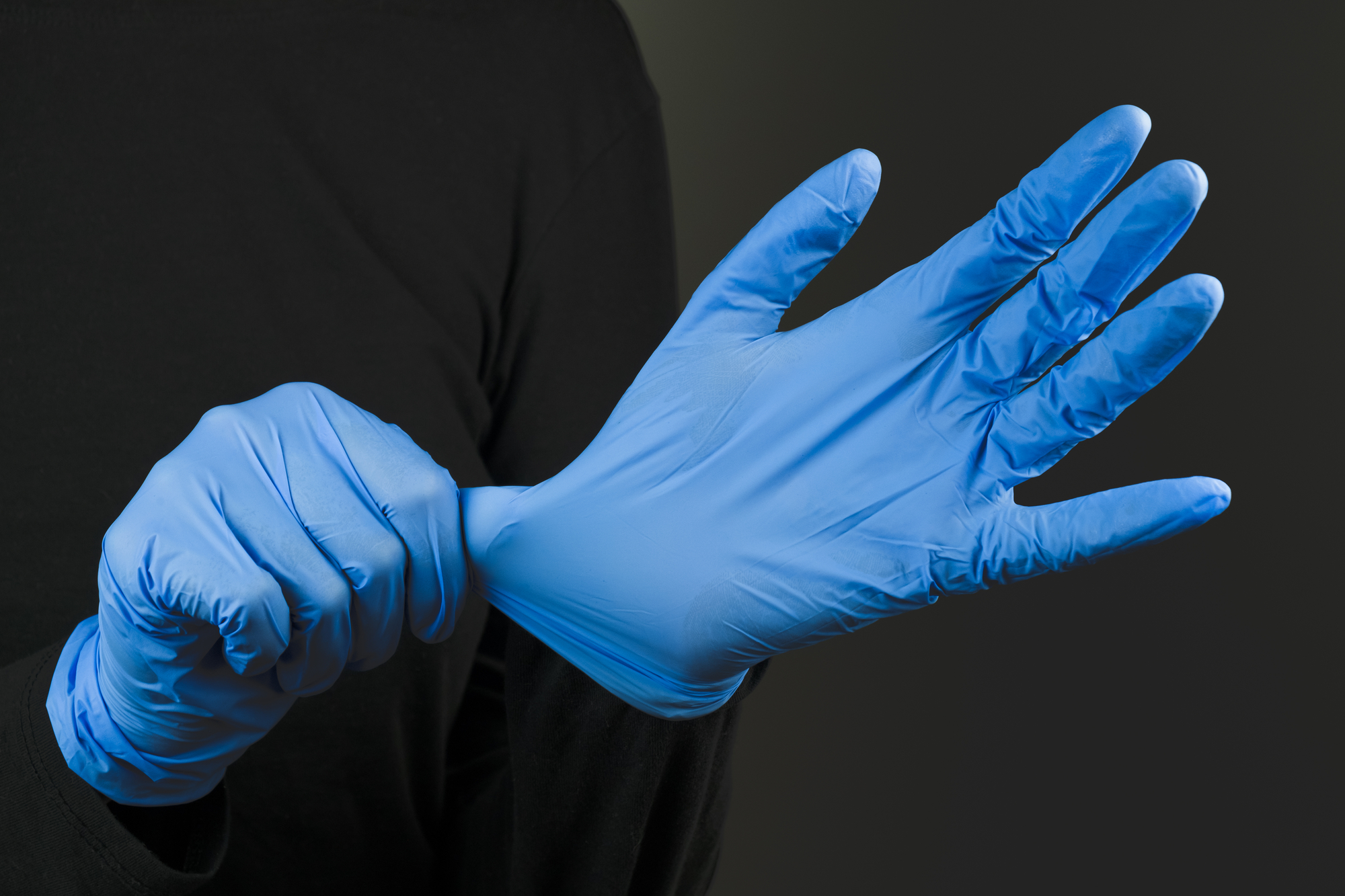 Putting on blue rubber hand gloves. Wearing protective hand gear against the infection or virus spread.