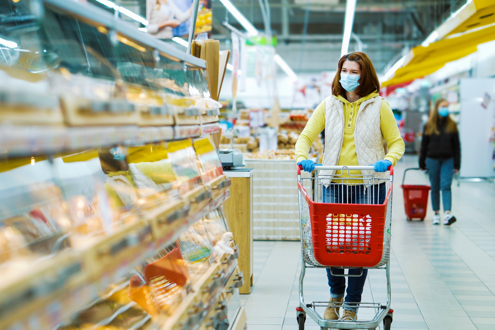 Young woman wearing medical mask and gloves with shopping cart walking along aisles with fresh bakery.