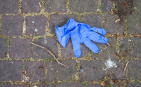 Closeup of blue used latex glove abandoned in the street during